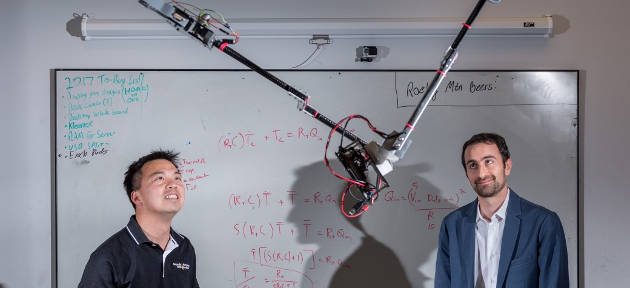 Tarzan-robot-swinging: Researchers Jonathan Rogers and Ai-Ping Hu are shown with the Tarzan robot in a Georgia Tech lab. The robot will swing from cables to inspect crops in the field. Photo Credit: Jason Maderer, Georgia Tech