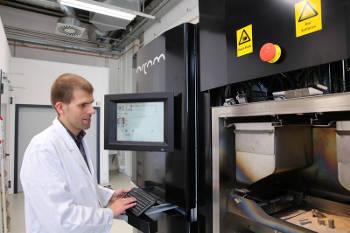 Prof. Dr. Thomas Niendorf vor einem 3D-Metall-Drucker (mit älteren Produkten). Foto credit: Andreas Fischer.