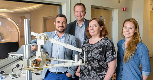 Fabrizio Sergi stands in front of the MRI exam room with his wrist-controlled robotic device. With him stands co-investigators Curtis Johnson and Susanne Morton as well as doctoral student Andria Farrens. Photo by Evan Krape