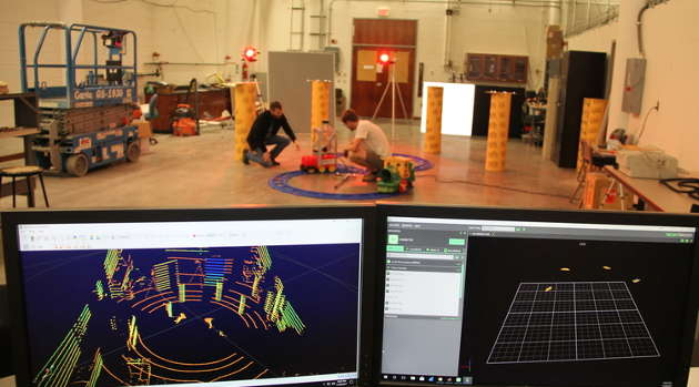 NavLab manager Nick Morris (left) and undergraduate researcher Nicholas Patzke set up a test vehicle that is tracked by a Vicon camera and a lidar system, seen on the monitors in the foreground. (Photo credit: Pete Brown/UA College of Engineering)