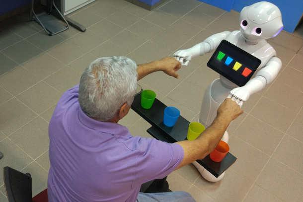 Ein Roboter beglückwünscht einen Patienten, weil dieser farbige Becher nach einer Vorgabe korrekt sortiert hat. Foto credit: Shelly Levy-Tzedek