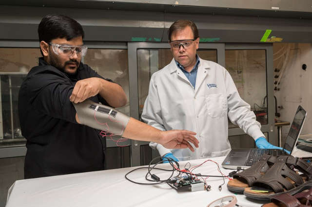 Sagar Doshi (left) and Erik Thostenson test an elbow sleeve outfitted with one of their novel sensors. Photo by Kathy F. Atkinson