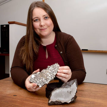 Princeton seismologist Jessica Irving, an assistant professor of geosciences, sits with two meteorites from Princeton University's collection that contain iron thought to be from the cores of planetesimals. We have no samples of Earth's own core to study, so Irving uses seismology to investigate the deepest regions of the planet, recently developing a new model for the Earth's outer core. Photo by Denise Applewhite, Office of Communications