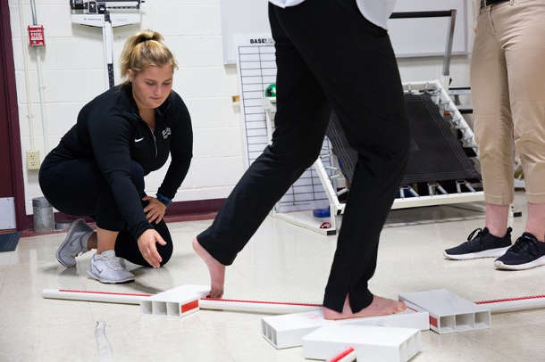 Alissa Strouse conducts research on what is known as the Y-Balance Test, to determine its usefulness in assessing the effects of a concussion. Photo by Ashley Barnas